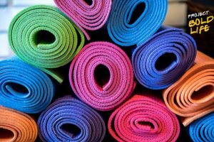 A bunch of yoga mats stacked up